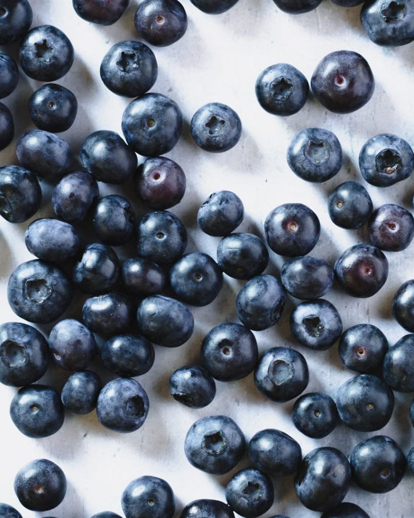 fresh blueberries viewed topdown on light blue background